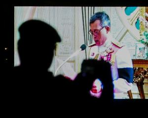 A soldier takes a photo as a television screen shows Thailand's new King Maha Vajiralongkorn...