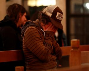 A woman weeps during a vigil at the Chapel of the Chimes for victims of the fire in the Fruitvale...
