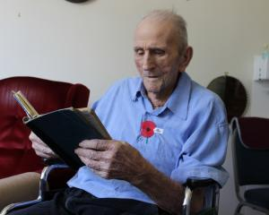 Cromwell centenarian Jack Robertson reads through his World War 2 Bomber Command logbook. Photo:...