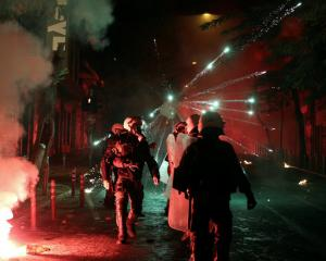 Fireworks explode next to riot police during clashes following an anniversary rally marking the...
