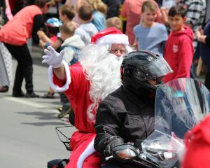 Santa waves to the crowd as he rides a motorcycle, instead of his traditional reindeer and sleigh...
