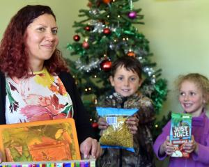 Danielle Culling and her children Felix and Alba put presents in a box in their Dunedin home to...