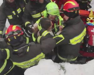 Rescuers with a survivor of the avalanche at Hotel Rigopiano in Farindola, central Italy. Photo...