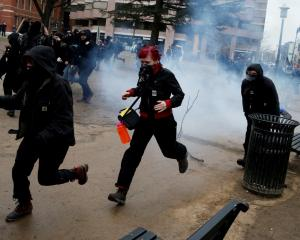 Activists run after a stun grenade went off during protests against Donald Trump on the sidelines...