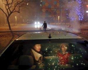 A girl and a woman sit inside the car as firecrackers and fireworks explode celebrating the start...