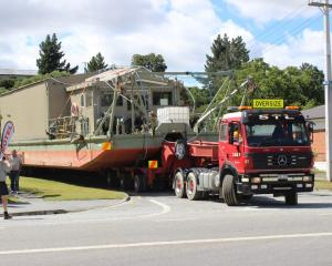 A gold dredge is towed through Roxburgh as it is moved from the town to Beaumont yesterday. Photo...