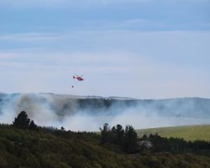 Helicopters fight the blaze in the hills behind Kaitangata as seen from Macrocarpa Rd. PHOTO:...