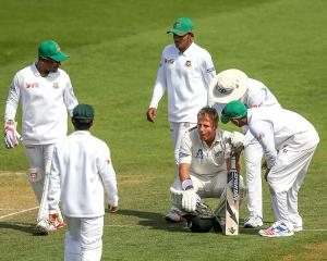 Bangladesh players check on Neil Wagner after he was hit with a bouncer. Photo: Getty Images