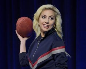 Lady Gaga poses with a football during the Super Bowl LI halftime show press conference in...
