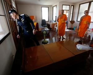 A policeman and Buddhist monks search for a fugitive Buddhist monk inside Dhammakaya temple in...