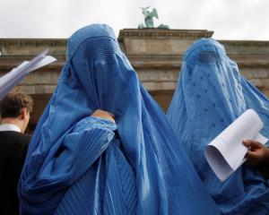 Protestors dressed in traditional burqa garments attend a demonstration against the deployment of...