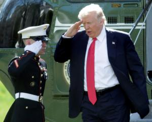 US President Donald Trump salutes from the steps of Marine One helicopter on the South Lawn of...