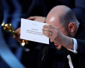 """Producer Jordan Horowitz holds up the card for the Best Picture winner """"Moonlight"""". Photo Reuters"""