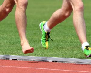 The bare feet of Danny Baillie chase the spikes of Aaron Anderson in the Otago 5000m...