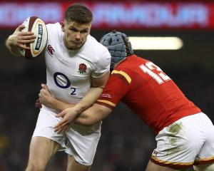 Owen Farrell of England is tackled by Jonathan Davies of Wales during their RBS Six Nations match...