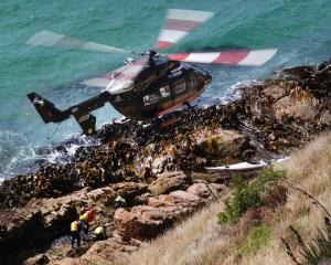 A helicopter hovers over rescuers attending to one of two kayakers trapped on rocks at Nugget...