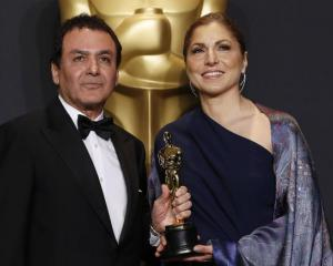 Anousheh Ansari and Firouz Naderi pose with the Oscar they accepted on behalf of Asghar Farhadi....