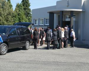 Mourners gather as Russell Glendinning's coffin is carried from the Lumsden Memorial Hall. Photo:...