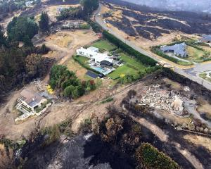 Surrounded by devastation, a helicopter fighting the Port Hills fire in Christchurch this week...