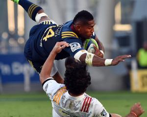 Highlanders winger  Waisake Naholo tries to evade the clutches of his  Chiefs opposite,  James...