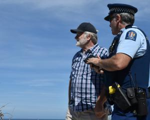 A police officer speaks to witness Ray Green after a tourist was caught in a rip at St Clair...