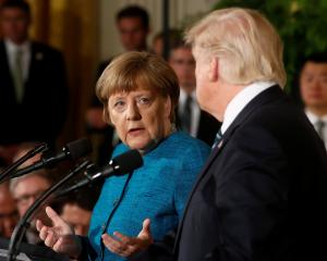 German Chancellor Angela Merkel makes her case to United States President Donald Trump during a...