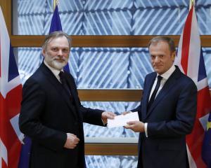 Britain's permanent representative to the European Union Tim Barrow (left) delivers British Prime...