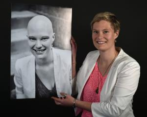 Anna Hoek-Sims, holds a photo of her 22-year-old self when she was being treated for cancer, in...