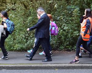 Dunedin Mayor Dave Cull walks to school with Arthur Street School pupils along Maori Rd yesterday...
