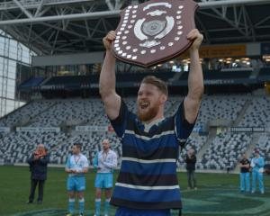 Kaikorai captain Blair Tweed holds up the trophy after leading his side to a win over Dunedin in ...