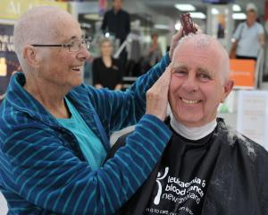 Kevin Bayne lets his wife Coleen shave his head as a show of support after she survived blood...