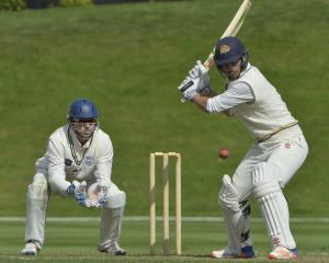 Otago century-maker Anaru Kitchen gets ready to dispatch the ball as Auckland wicketkeeper Ben...