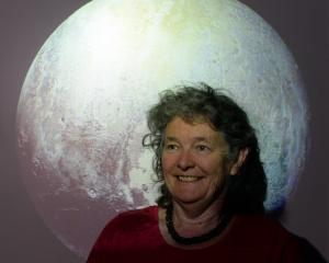 New Horizons co-investigator Fran Bagenal with an image of Pluto, captured by the New Horizons...