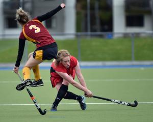 Millie Cowan, of Momona, powers the ball towards the net as Southland Barbarians' Aimee Heaps jumps to get out of the way in a match at the McMillan Hockey Centre on Saturday. Photo by Peter McIntosh.