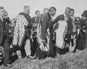 Pall-bearers carry the coffin of the late Hon T. Parata up the hill to his last resting place in...