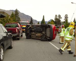 Queenstown volunteer firefighters attend the scene where a vehicle overturned yesterday. Photo by...