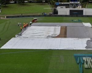 Ground staff adjust the covers as rain delays the start of day five of the Test match between New...