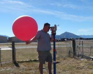 Nasa meteorologist Chris Schwantes checks wind speed and direction before releasing a pilot...
