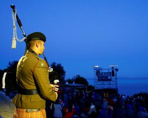 A bagpiper performs during a dawn ceremony at Anzac Cove on the Gallipoli peninsula in Turkey,...