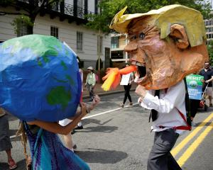 Protesters dressed as Earth and US President Donald Trump pretend to fight during the march....