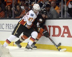 Calgary Flames defenceman Dougie Hamilton (left) pins Anaheim Ducks centre Rickard Rakell against...