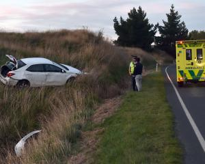 Police and Ambulance at the scene of a car accident North of Waihola on Tuesday. PHOTO PETER MCINTOSH