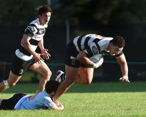 Southern No 8 Mika Mafi tries to slip a tackle by University's Connor McLeod during a premier match at Logan Park on Saturday. Josh Walden is the player in support. Photo by Peter McIntosh.