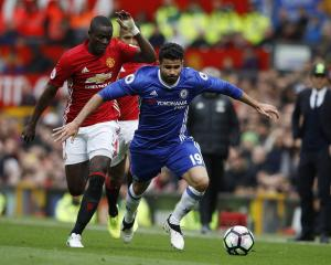 Chelsea's Diego Costa with the ball as Eric Bailly chases him in their game against Manchester...