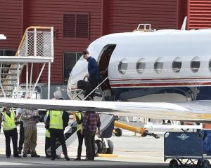 FBI director James Comey emerges from a Gulfstream G550 jet at Queenstown Airport yesterday to take part in a spy conference at the resort this week. Photo: Craig Baxter.