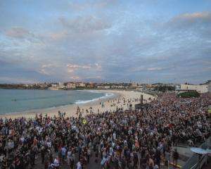 People gather for the Anzac Day dawn service at North Bondi beach in Sydney this morning. Photo...