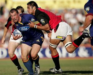 Otago Highlander Paul Miller looks to offload while in the tackle of Crusaders lock George Naoupu...