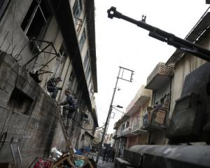 A member of the Iraqi Federal Police climbs up a ladder in a street next to the frontline during combat with Islamic State in western Mosul. Photo: Reuters