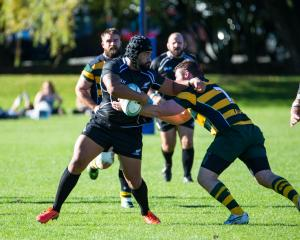 New Zealand Police Rugby side's Glen Potoi attempts to fend Australia Police's Mitch Greig, at the Queenstown Recreation Ground yesterday. Photo: James Allan.