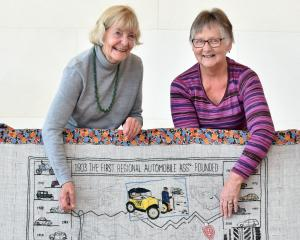 During a public stitching event at Toitu Otago Settlers Museum, Dunedin embroiderers Jeanette Trotman (left) and Judy Mason display a stitched panel devoted to the founding of New Zealand's first regional Automobile Association, in Otago. Photo: Peter McI